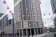 Beneath a high-rise of residential apartments, pink spherical lanterns hang from cables above the A11 in Stratford during the second wave of the Coronavirus pandemic, on 26th November 2020, in London, England. Stratford was the home iof the London 2012 Olympics where industrial estates centred around Carpenters Road were demolished to make way for sports venues  and now, after 8 years, for extensive housing.
