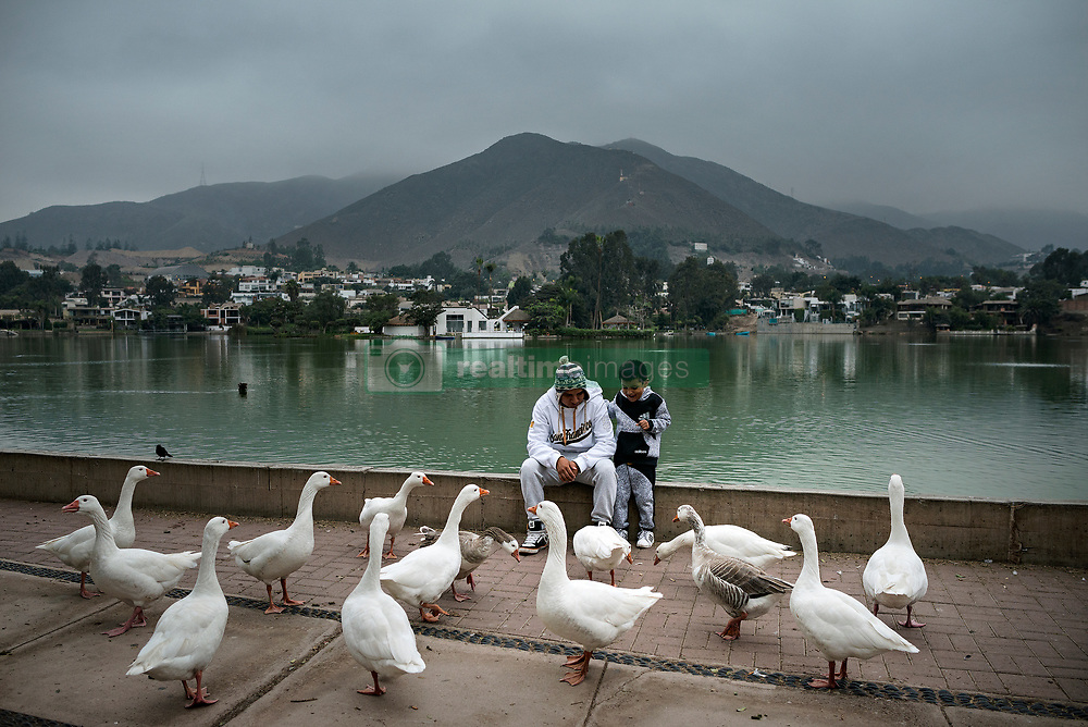 NO WEB/NO APPS - (Text available) Father and son are seen playing with ducks nearby an artificial lake next to the luxury urbanization, in Lima, Peru in May 2017. In Peru's capital Lima, a three-meter-high concrete wall topped with reels of razor wire separates two areas. The so-called 'Wall of Shame' - sometimes nicknamed 'Peru's Berlin Wall' - divides the urbanisation of Las Casuarinas, where some of the country's richest inhabitants live, and the poor suburb of Vista Hermosa next door. It was initially put up over fears that the inhabitants from the poor neighbourhood would steal from wealthy fellow citizens living nearby. On the rich side of the wall, the price for a square meter can exceed 2,000 dollars. To enter the area, you must show your ID to the guards watching the gate at the bottom of the hill. Former high-ranking politicians and bank directors live here. Their houses are surrounded by lush gardens and swimming pools despite the scarcity of water. Meanwhile, on the San Juan de Miraflores side, residents often fall victim to robbery and theft. They live in houses of barely 25m², made from scrap material, surrounded by the sand and earth characteristic of Lima's desert landscape. Photo by Giacomo D'Orlando/ABACAPRESS.COM