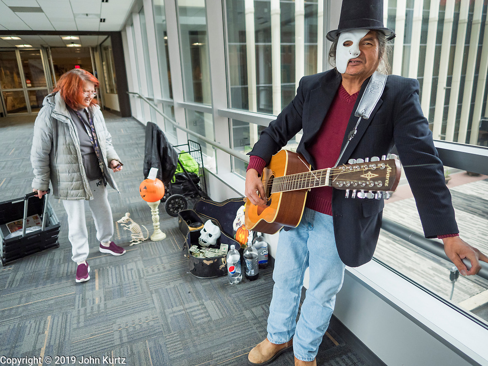 """30 OCTOBER 2019 - DES MOINES, IOWA: RANDY KONG talks about performing in the Des Moines Skywalk system. Kong said he's been busking for about nine years. He said he started when his band broke up and busking might be way to """"get a hot dog and a coke, and now it's turned into a career."""" He is a regular sight in the skywalk system. In October he hands out candy and sings Halloween themed songs while wearing a """"Phantom of the Opera"""" like mask. In December he does a Christmas themed show and in February he does a Valentines themed show.          PHOTO BY JACK KURTZ"""