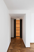 Detail of corridor and open closet. White wall