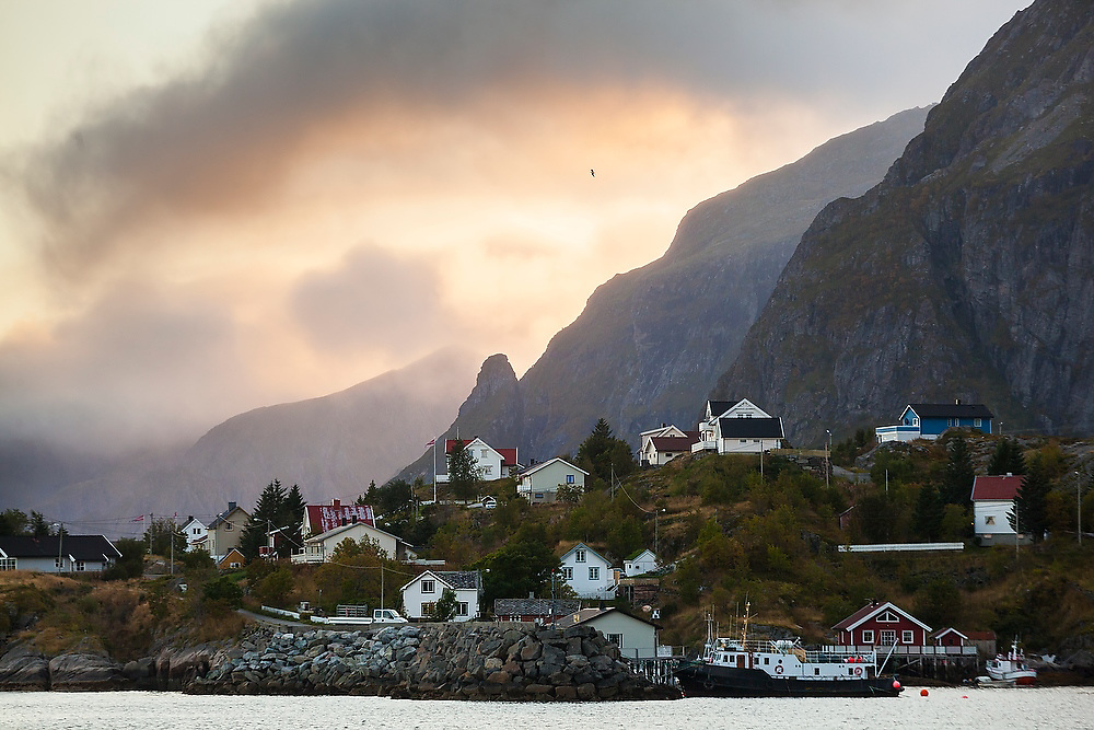 High mountains loom over homes in Moskenes, Lofoten Islands, Norway.