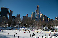 New York. central Park under the snow. Wollman Skating Rink  in the distance the skyline of central park south i/ piste de patinage dans Central park Wollman Skating Rink et les gratte-ciels, New York - Etats-unis