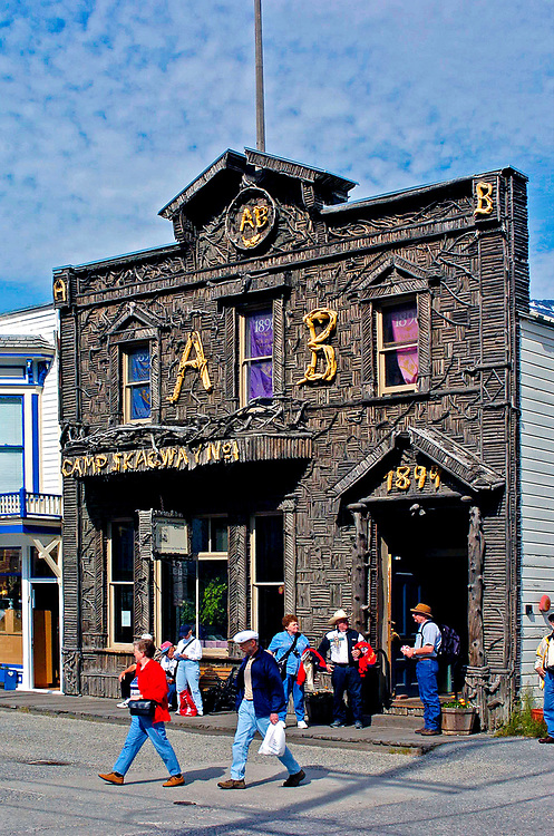 Alaska, Skagway.Visitors check out the AB Building covered in driftwood.