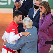 PARIS, FRANCE June 13.   Novak Djokovic of Serbia receives the winners trophy from Bjorn Borg as a disappointed runner up Stefanos Tsitsipas of Greece stands close by at the presentation on Court Philippe-Chatrier after the final of the singles competition at the 2021 French Open Tennis Tournament at Roland Garros on June 13th 2021 in Paris, France. (Photo by Tim Clayton/Corbis via Getty Images)