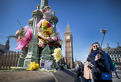 © Licensed to London News Pictures. 26/03/2017. London, UK. A couple take a selfie next to a flowers placed on a lamppost on Westminster Bridge. Hundreds of floral tributes have been placed on the fences and gates surrounding Parliament in memory of those killed in the Westminster terror attack earlier this week. Photo credit: Peter Macdiarmid/LNP
