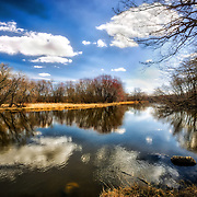 Blue sky and clouds are being reflected on the water surrounded by trees in this Wisconsin landscape image.