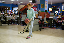 Elderly woman on the approach of the ten pin bowling lane getting ready to make a strike,
