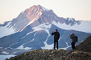 Lukasz (left) and Rafal Flieger take pictures from Arieskaret Pass on a sunset hike above the Polish Polar Station in Hornsund, Svalbard. Wienertinden rises in the distance.