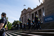 Police move into position on the steps of state parliament ahead of a planed protest. The groups who have organised the many Freedom Day protest over the last 3 months, attempted to march to State Parliament on Melbourne Cup Day demanding the sacking of Premier Daniel Andrews for the lockdown and attacks on their civil liberties, where they were met with a heavy police presence.  (Photo by Michael Currie/Speed Media)