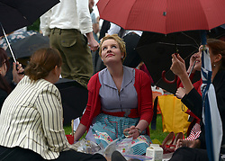 © Licensed to London News Pictures. 07/07/2012. London, UK  A woman looks at the rain at 'The Chap's Olympiad' in central London on July 7th, 2012. 'The Chap' is a light-hearted magazine, aimed at revisiting the fashions and pastimes of the polite aspects of 1920's to 1950's England. The annual Olympiad event sees competitors take part in events such the 'Cucumber Sandwich Discus', 'The Umbrella Joust' and 'The Tug of Hair'e. Photo credit : Stephen Simpson/LNP