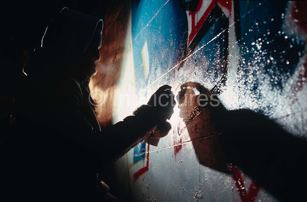 Viewed from a low angle, an unidentified youth is seen spraying graffiti art on to a wall in the Notting Hill area of West London, England. We see his partially-obscured face lit from behind with a strong amount of flash which throws a well-defined shadow of his hand holding a spray can. It is a chilly night and the boy's breath is seen against the frosty night air. His graffiti art has taken him some hours to spray on this white wall and shows a glossy finish. The picture is anonymous because of the young man's face is unseen and generic, because we don't see where the wall might be located.