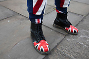 Leave means leave pro Brexit anti Europe demonstrator wearing patrioric Union Jack flag Dr Marten boots in Westminster opposite Parliament on the day MPs vote on EU withdrawal deal amendments on 29th January 2019 in London, England, United Kingdom.