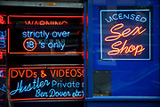 Neon signs in the windows of a sex shop adult entertainment store in London's red light district of Soho.