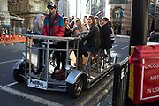 Stag party with male and female guests cycle a pedibus around the City of London, UK. Sitting at a table and pedalling away, while drinking, this is a common site around the area.