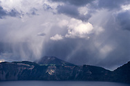 Sunlit rain downpour from storm clouds, Crater Lake National Park, Oregon