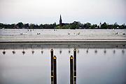 Nederland, Nijmegen, 16-4-2020 Vier palen in de Spiegelwaal op het rivierpark Veur-Lent markeren de plek waar in de 80-jarige oorlog de ophaalbrug van fort Knodsenburg lag. Op een paar meter stenen van de fundering na is niets meer van het fort bewaard gebleven . Foto: Flip Franssen