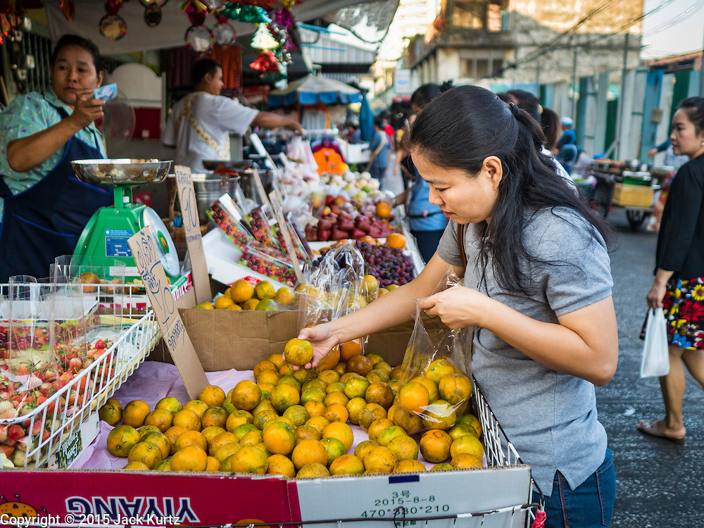 30 DECEMBER 2015 - BANGKOK, THAILAND:  A woman shops for oranges at a stall next to Bang Chak Market. The market is supposed to close permanently on Dec 31, 2015. The Bang Chak Market serves the community around Sois 91-97 on Sukhumvit Road in the Bangkok suburbs. About half of the market has been torn down. Bangkok city authorities put up notices in late November that the market would be closed by January 1, 2016 and redevelopment would start shortly after that. Market vendors said condominiums are being built on the land.           PHOTO BY JACK KURTZ