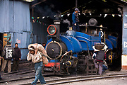 "Train workers prepare a steam train for the daily run from Kurseong back to Darjeeling. The Darjeeling Himalayan Railway, nicknamed the ""Toy Train"", is a narrow-gauge railway from Siliguri to Darjeeling in West Bengal, run by the Indian Railways. It was built between 1879 and 1881 and is about 86 km long. The elevation level is from about 100 m at Siliguri to about 2200 m at Darjeeling. It is still powered by a steam engine and travels daily between the two towns.  It is now classed as a World Heritage Site by UNESCO. India."