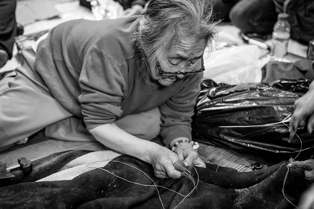 Nellie Nastapoka while she was sewing a seal skin for an umiak.
