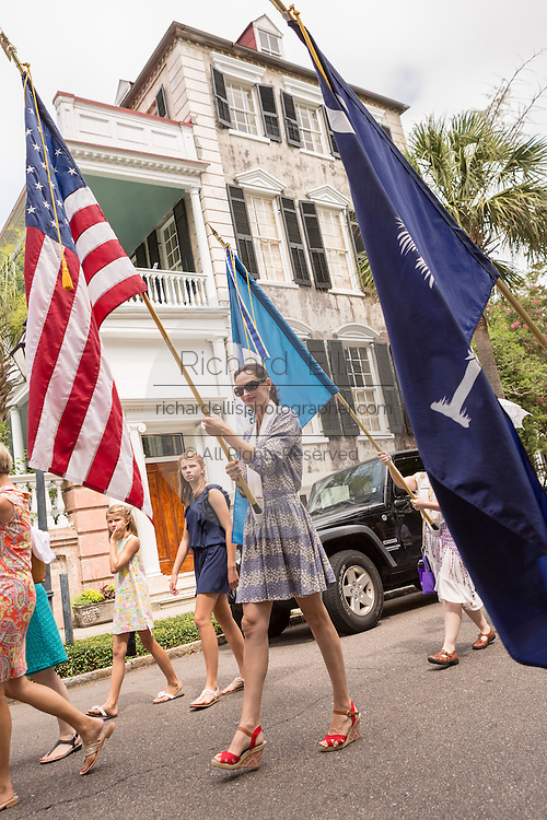 Women carrying flags march down Meeting Street to celebrate Carolina Day June 28, 2014 in Charleston, SC. Carolina Day celebrates the 238th anniversary of the American victory at the Battle of Sullivan's Island over the Royal Navy and the British Army.