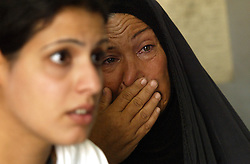 Alyaa Abdul Hassan Abbood, 23, a translator, tries to explain to a U.S. soldier that Beheyen Ibrahim Jar, crying behind her, just found out that her husband died at the hands of a U.S. soldier, Baghdad, Iraq, Sept. 27, 2003. Abbood works with the U.S. military to mediate as Iraqi civilians come in to receive monetary compensation for damages done by American troops in Baghdad.