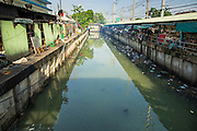 """26 SEPTEMBER 2012 - BANGKOK, THAILAND: Khlong Toey runs along Khlong Toey Market in Bangkok. Khlong is the Thai word for canal. This canal used to go all the way to the old imperial center of Bangkok but has been filled in now. This stretch of the canal is used for waste water from the market. Khlong Toey (also called Khlong Toei) Market is one of the largest """"wet markets"""" in Thailand. The market is located in the midst of one of Bangkok's largest slum areas and close to the city's original deep water port. Thousands of people live in the neighboring slum area. Thousands more shop in the sprawling market for fresh fruits and vegetables as well meat, fish and poultry.     PHOTO BY JACK KURTZ"""