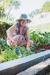 Happy woman working with a shovel in vegetable garden, Altoetting, Bavaria, Germany