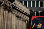 Columns of the Bank of England and young women top-deck bus passengers in the City of London.
