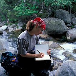 White Mountain N.F., NH.A woman takes a break from hiking to write in her journal.  Great Gulf Trail. Peabody River. Backpacking.