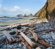 Pacific Ocean tides have strewn driftwood and logs near Sea stack rocks on the north side of the hiker's tunnel at Oceanside beach, Oregon, USA. Panorama stitched from 2 images.