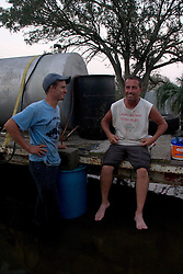 25 Sept, 2005.  Carlyss, Louisiana. Hurricane Rita aftermath. <br /> L/R Local man Aaron Stokes helps neighbour Harold Herman to syphon diesel fuel from a 500 gallon drum for use in Harold's generator. Locals helped each other through the aftermath of the storm. Harold wears a T-shirt that reads 'Laissez les Bon Temps Rouler' which translates to 'let the good times roll.'<br /> Photo; ©Charlie Varley/varleypix.com
