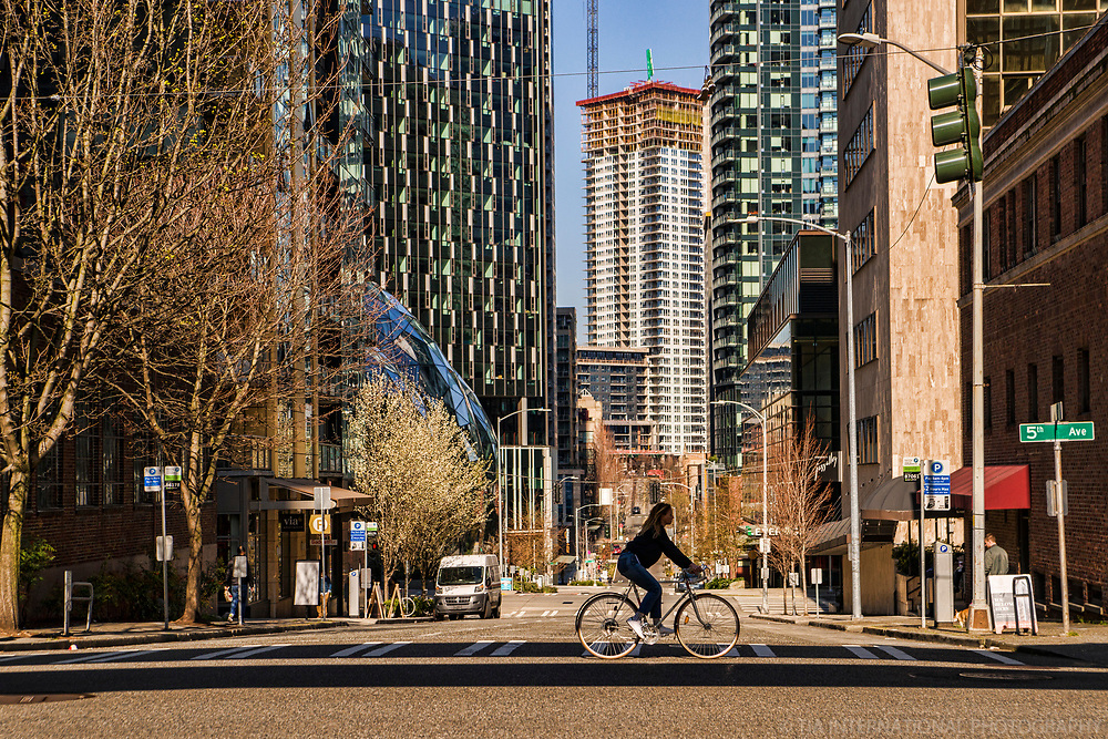 The cyclist riding along 5th Avenue actually blocks the sheer void of Lenora Street that stretches for several blocks away from the viewer's line of sight. For context to this phenomenon, to the left, you can see part of Amazon's Spheres and one of the towers of its massive world headquarters. (March 21, 2020)
