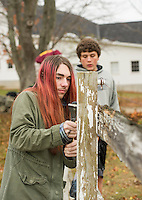 Jack Brown and Hunter Bean scrape the fence in preparation for a new coat of paint at the Meadows Field as part of the Gilford/Gilmanton Community Service Day on Tuesday.  (Karen Bobotas/for the Laconia Daily Sun)