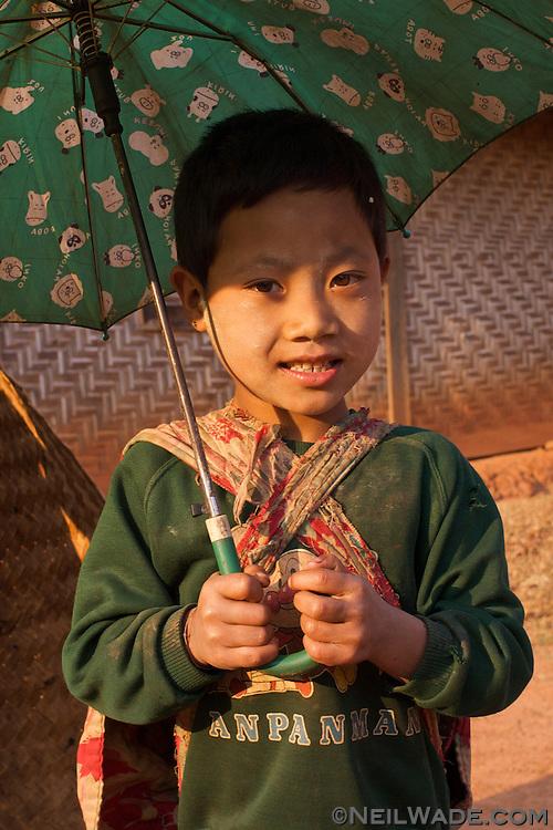 A Burmese child holding an umbrella.