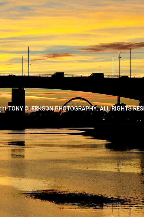Sunset lights up Glasgow along the River Clyde silhouetting the Kingston Bridge and the Clyde Arc, known locally as the Squinty Bridge