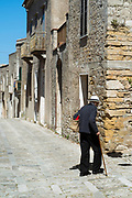 Street scene of back view of elderly man with walking stick and shopping bag in cobble stones alleyway, Erice, Sicily, Italy