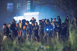 © Licensed to London News Pictures . 05/11/2015 . Oldham , UK . A large group of people engaging in anti-social behaviour , shooting fireworks at residences and lighting a bonfire ,  on grass between Stafford Street and Norfolk Street , in Chadderton . Manchester Fire reports receiving more than 300 calls in less than 7 hours, from 4.30pm, including to buildings, cars and wheelie bins set alight by arsonists . At some calls fire crews were subject to vandalism , including a hose being sliced whilst it was being used to fight a fire in Leigh and bricks being thrown at crews attending a job in Miles Platting . Fire crews deal with arson attacks across Greater Manchester during Bonfire Night . Photo credit : Joel Goodman/LNP