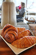 A plate with four croissants and out of focus people in the background unidentifiable people in the background