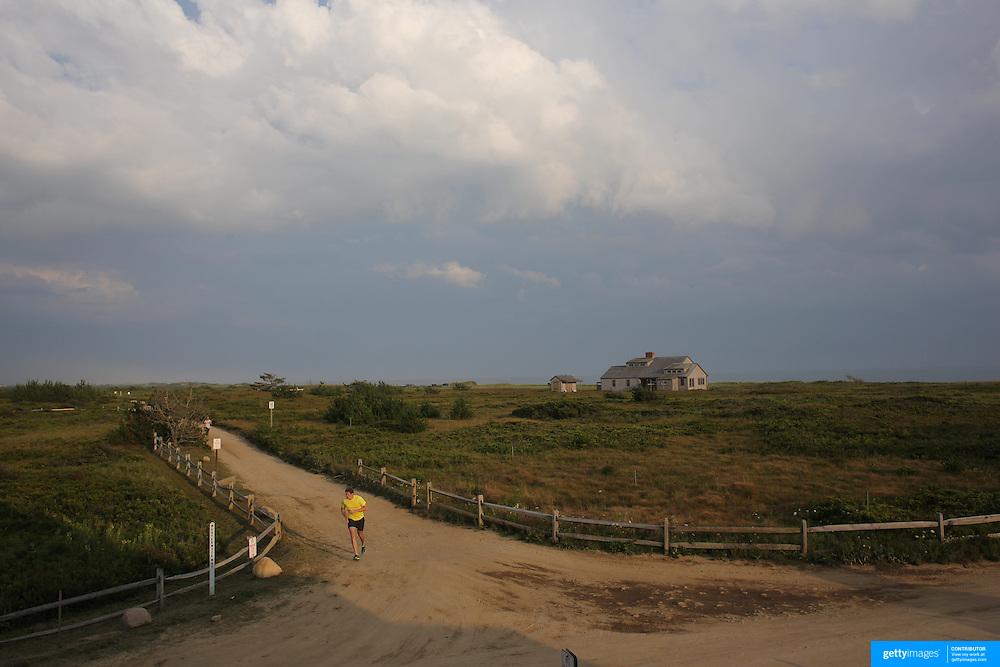 A jogger passes beachside properties on the coastline at Cisco Beach, Nantucket, Nantucket Island, Massachusetts, USA. Photo Tim Clayton