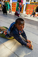 A Tibetan boy prostrating himself repeatedly as he circumambulates through Barkhor Square and along The Barkhor (around the area of the Jokhang Temple), the most sacred temple in Tibet, Lhasa, Tibet, China.