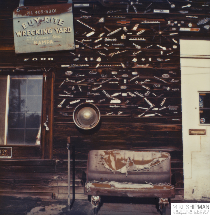 Automotive emblems and an old, torn, car seat adorn the old wood siding of an auto repair shop in Nampa, Idaho