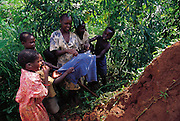 Children in the village of Bweyogerere hunt for termites by hacking into their earthen mound, placing a cloth in front of the entrance, and collecting the ants that attack the cloth. Bweyogerere, Uganda. (Man Eating Bugs page 148 Top)