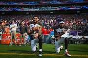 """Tampa Bay Buccaneers wide receivers Mike Evans (L) and DeSean Jackson kneel during the national anthem, in protest to comments made by President Donald Trump, before an NFL game against the Minnesota Vikings at U.S. Bank Stadium in Minneapolis, Minnesota, U.S., September 24, 2017. During a rally in Alabama two days earlier, Trump told supporters that NFL owners should respond to players like Colin Kaepernick kneeling during the anthem by saying, """"Get that son of a bitch off the field right now, he's fired. He's fired!"""""""
