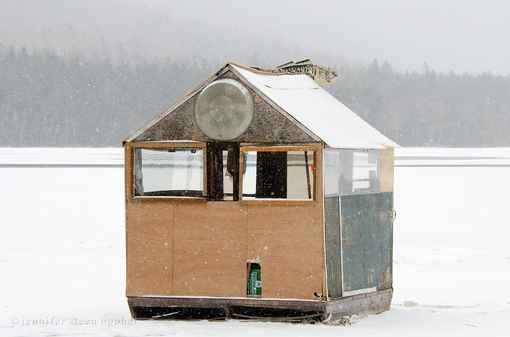 A battered, makeshift ice fishing shack in a snowstorm.