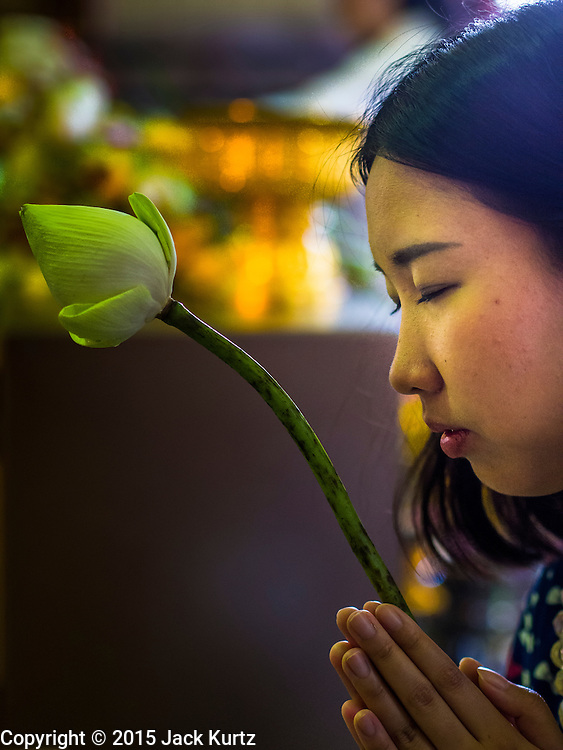 """04 MARCH 2015 - BANGKOK, THAILAND: A woman prays in the """"wiharn"""" or prayer hall at Wat Benchamabophit on Makha Bucha Day. Makha Bucha Day is an important Buddhist holy day and public holiday in Thailand, Cambodia, Laos, and Myanmar. Many people go to temples to perform merit-making activities on Makha Bucha Day. Wat Benchamabophit is one of the most popular Buddhist temples in Bangkok.    PHOTO BY JACK KURTZ"""