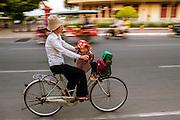 Een vrouw fietst met een klein kind voorop door het oude centrum van Phnom Penh.