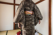 JAPAN, TOKYO Antique Kimono Oshima Tsumugi type from Amami Oshima in Okinawa. The kimono is made by woven natural brown hempy fabric, and the obi is red with embrodery flowers. Photo during the dressing   - June 2014