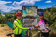 Cyclists and interpretive map at Lake Wanaka, Otago, South Island, New Zealand