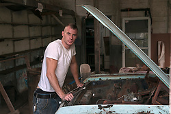 portrait of man working on an old car in a garage