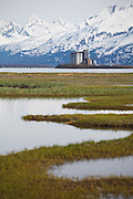 The Chugach Mountains rise above the Valdez Grain Terminal, built on an island in Port Valdez, Alaska.